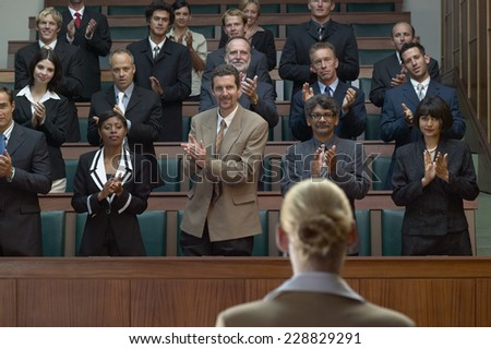 Audience of businesspeople applauding a businesswoman - stock photo