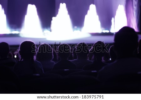 Audience seated in an auditorium or theatre watching a live performance on stage with performers appearing as bright areas of light - stock photo