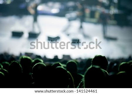 Audience watches a band performing live during a concert in a big auditorium - stock photo