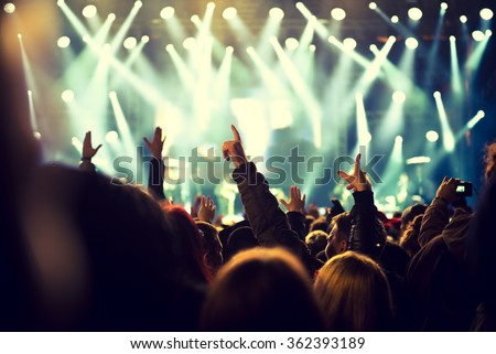 Audience with hands raised at a music festival and lights streaming down from above the stage - stock photo