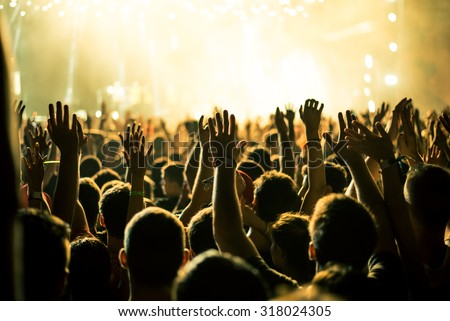 Audience with hands raised at a music festival and lights streaming down from above the stage. Soft focus, blurred movement. - stock photo