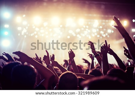 Audience with hands raised at a music festival and lights streaming down from above the stage. Soft focus, high ISO, grainy image. - stock photo