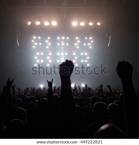 Audience with hands raised at a rock concert