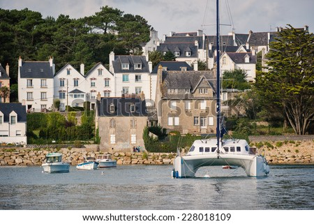 AUDIERNE, FRANCE - AUGUST 12, 2014: Catamaran in the harbor in a sunny day. Audierne lies on a peninsula at the mouth of the Goyen river and for centuries was a fishing village. - stock photo