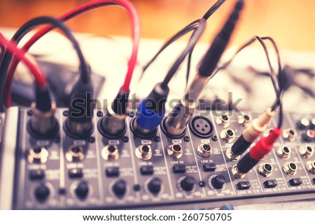 Audio and video jack cable connected at rear end of receiver, amplifier or music mixer at concert, party or festival. Soft effect on photo - stock photo
