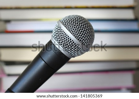 Audio books narration recording vocal microphone against background of books - stock photo