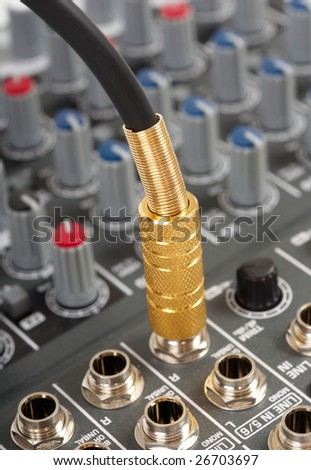 Audio cable with golden jack and control console - stock photo