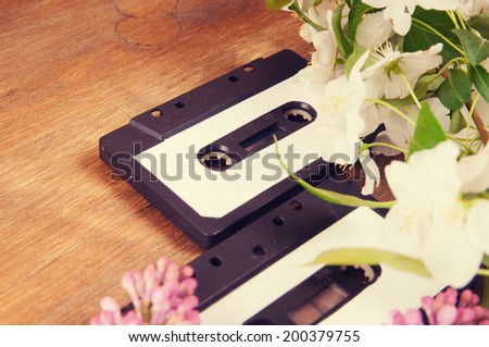 Audio cassette and spring flowers on a wooden table