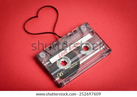 Audio cassette tape on red backgound. Film shaping heart, Valentine postcard. Label text love songs. - stock photo