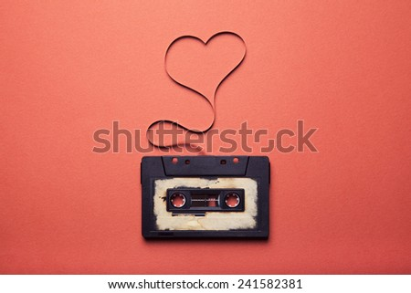 audio cassette with magnetic tape in shape of heart - stock photo