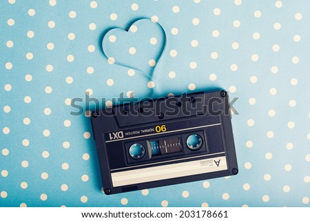 audio cassette with magnetic tape in shape of heart on blue dot polka background