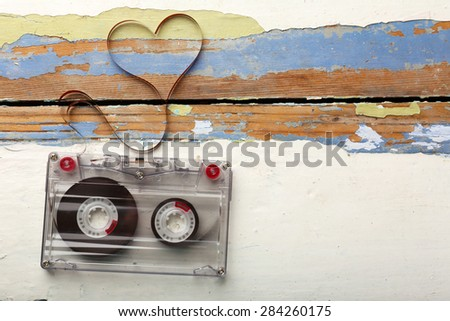 Audio cassette with magnetic tape in shape of heart on wooden background - stock photo