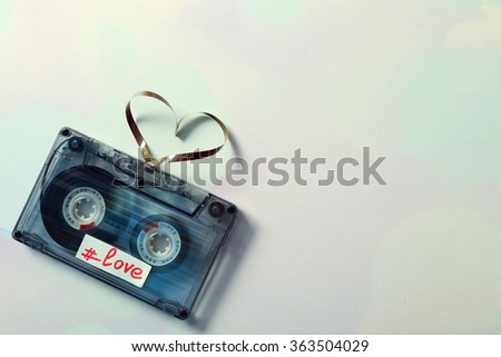 Audio cassette with magnetic tape in shape of hearts on light background - stock photo