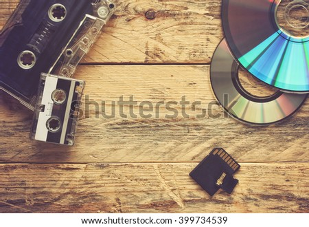 audio cassettes and two cd discs and flash cards on a wooden table - stock photo