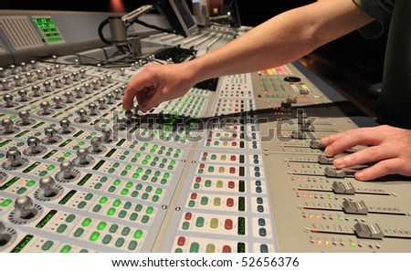 Audio engineer operating mixing console with hands - stock photo