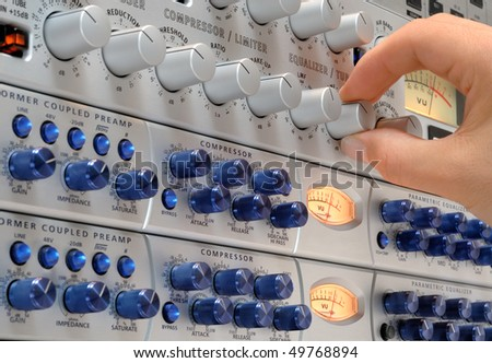Audio engineer's hand operating studio devices for a music production - stock photo