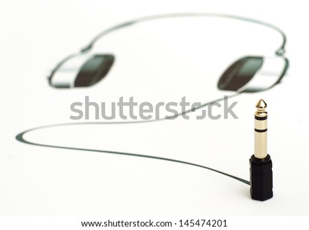 Audio jack connected to a printed set of headphones - stock photo
