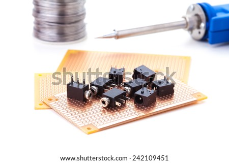 audio jack female placed on the pcb. Electronic printed board. Soldering iron is background - stock photo