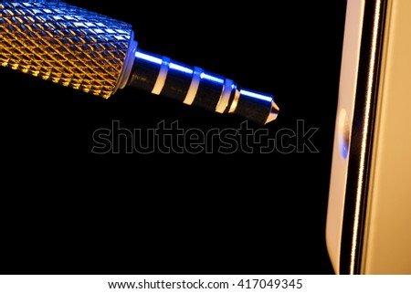 audio jack is connected to a mobile phone isolated on a black background executed in macro technique - stock photo