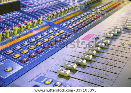 Audio mixer mixing board fader and knobs, Music mixing console with backlit buttons. Focus on detail, selective focus. - stock photo