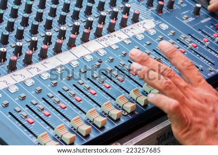 Audio mixing console closeup with hand