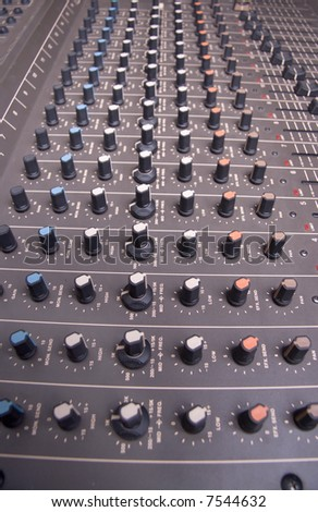 Audio mixing console shot from dramatic closeup wide-angle