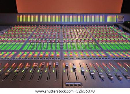 audio post production mixing console with lights on - stock photo
