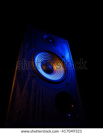 audio speaker illuminated in blue and orange on a black background isolated - stock photo