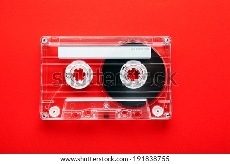 Audio tape cassette on red background - stock photo