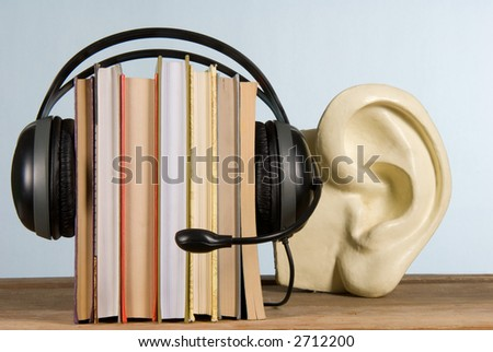 audiobook conception with headphones and books - stock photo