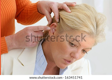 audiology specialist fixing hearing hair to a nice middle aged woman - stock photo