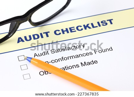 Audit checklist with ballpoint pen and glasses - stock photo