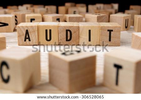AUDIT word written on wood block - stock photo