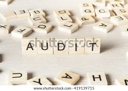 AUDIT word written on wood block. Wooden Abc.