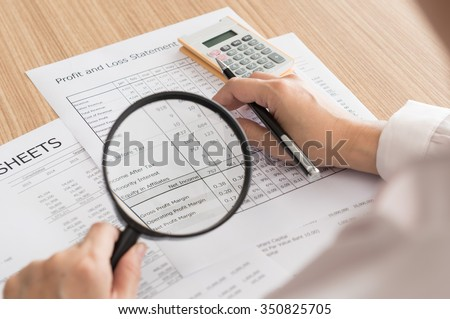 auditor checking financial statement with magnifying glass. - stock photo