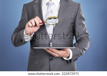 Auditor holding magnifying glass and tablet. Over blue background - stock photo