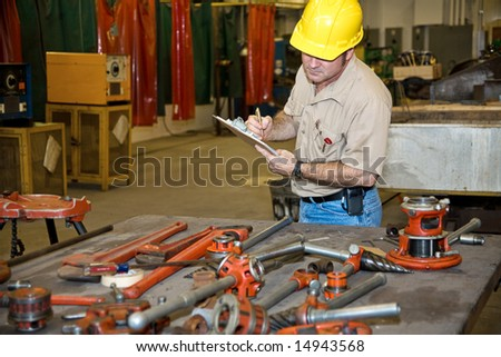 Auditor taking inventory of tools in an industrial factory.  Welding equipment is visible in the background. - stock photo