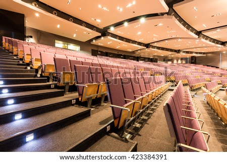 Auditorium with rows of comfortable, wood chairs and stairs - stock photo