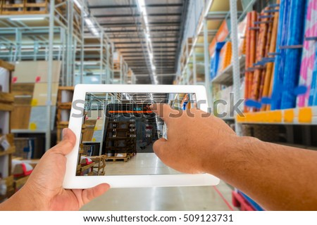 Augmented reality in warehouse and logistic concept. Hand hold and touching digital tablet with smart inventory application on screen in the warehouse.
