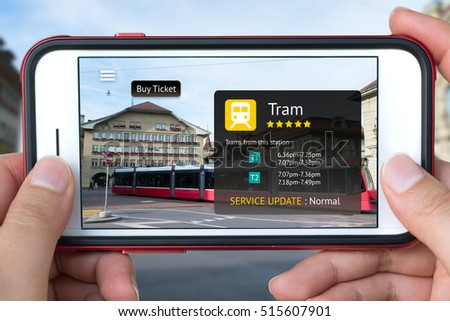 Augmented reality marketing concept. Hand holding smart phone use AR application to check schedule timeline of Tram and buy ticket. City and tram background