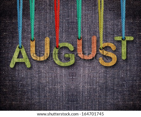 August letters hanging strings with blue sackcloth background. - stock photo
