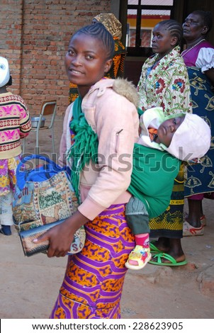 August 2014 - Pomerini - Tanzania - Africa - An African woman with her baby in traditional band, followed by the non-profit organization Mawaki to Fight AIDS, in the Franciscan Mission of Pomerini - stock photo