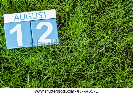 August 12th. Image of august 12 wooden color calendar on green grass lawn background. Summer day. Empty space for text.