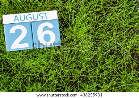 August 26th. Image of august 26 wooden color calendar on green grass lawn background with soccer ball. Summer day. Empty space for text