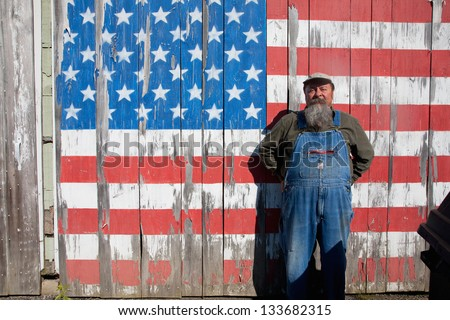 AUGUSTA - JUNE 10: Elderly man poses in front of US flag painted on his shed on June 10, 2012 near Augusta, Maine