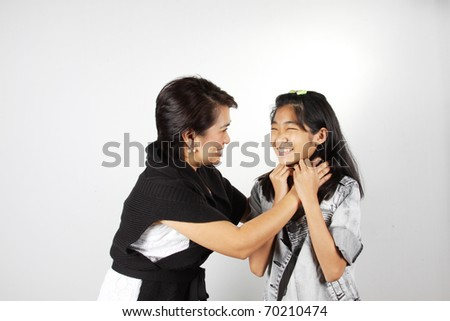 Auntie tease her granddaughter and the kid is laughing. - stock photo