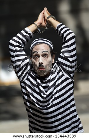 AURILLAC, FRANCE - AUGUST 21: a handcuffed clown wears  a striped costume as part of the Aurillac International Street Theater Festival, Cie Les hommes papillon,on august 21, 2013, in Aurillac,France  - stock photo