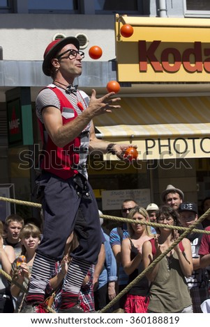 AURILLAC, FRANCE - AUGUST 19: a juggler balancing on a rope is playing with four red balls, as part of the Aurillac International Street Theater Festival, on august 19, 2015, in Aurillac,France.