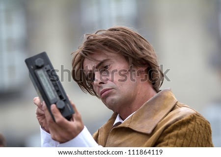 AURILLAC, FRANCE - AUGUST 24 : a pensive actor is looking at a car radio as part of the Aurillac International Street Theater Festival, Company En Estafette , on august 24, 2012, in Aurillac,France. - stock photo