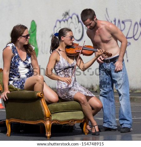 AURILLAC, FRANCE - AUGUST 22: a street performer plays the violin  as part of the Aurillac International Street Theater Festival, Company Monsieur Linea,on august 22, 2013, in Aurillac,France  - stock photo